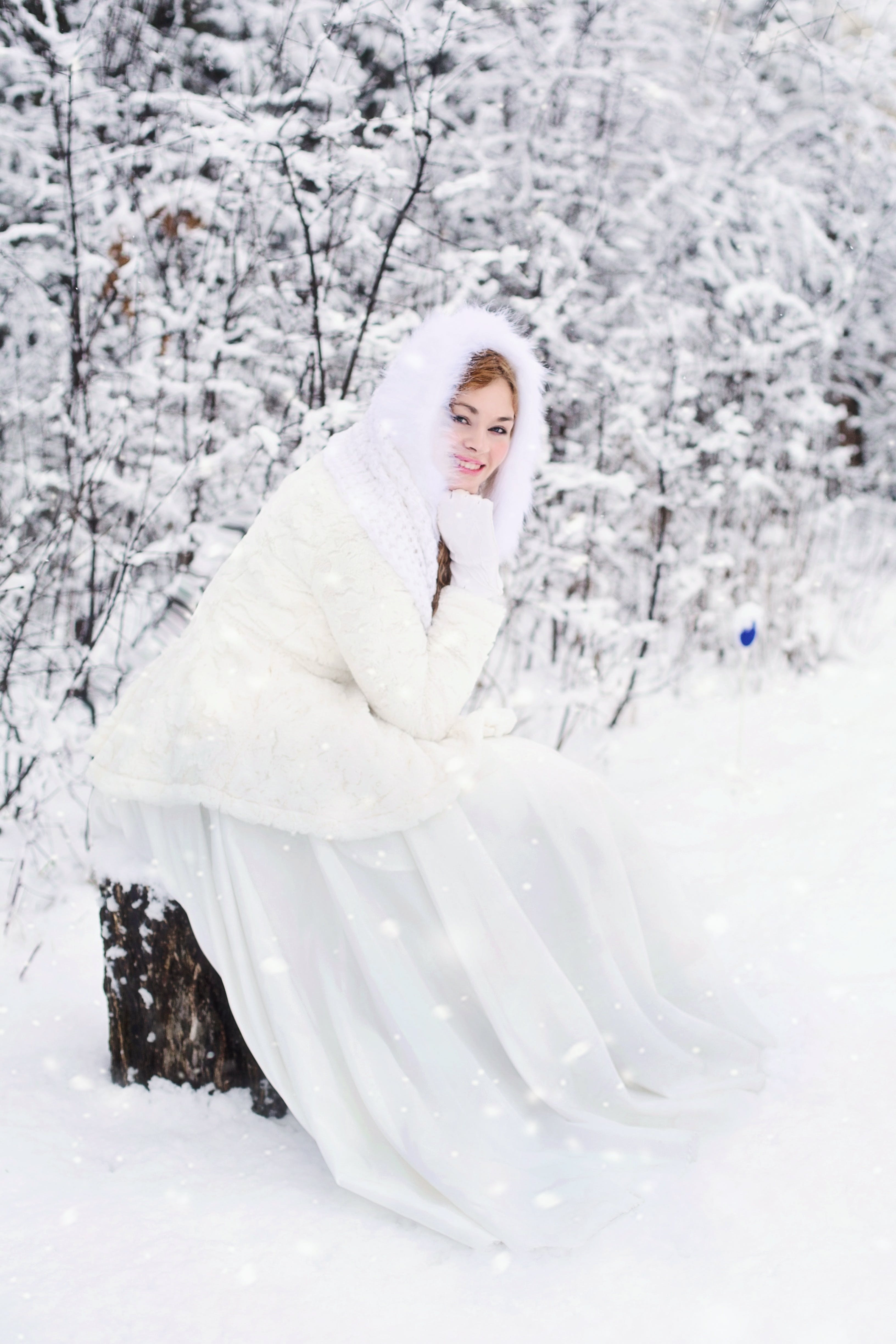 Woman in White Fur Hooded Dress in White Snow Filed