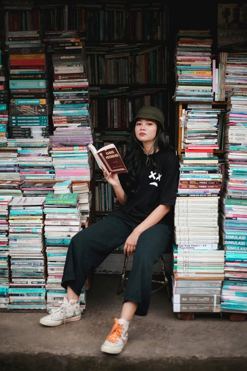 Woman in Black Crew Neck T-shirt Sitting on Books