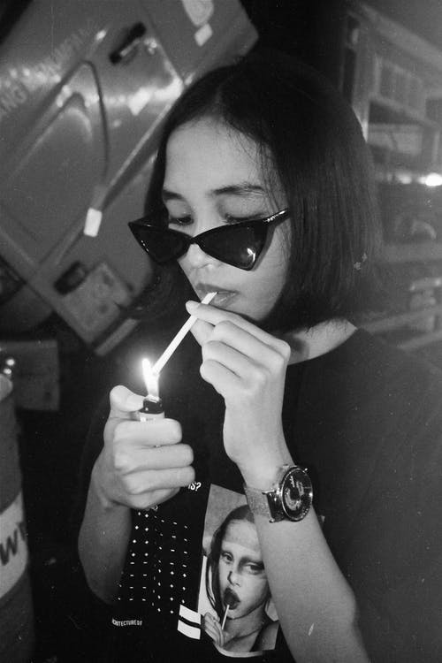Black and white of young trendy ethnic female millennial in stylish outfit and sunglasses lighting cigarette