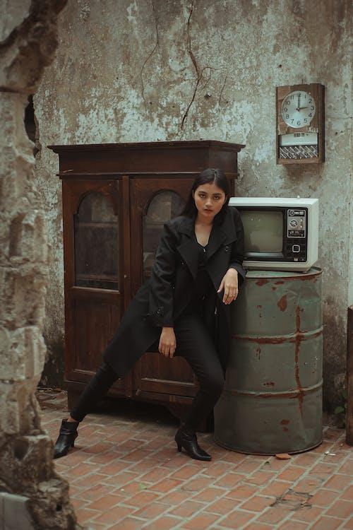 Woman in Black Suit Leaning on Rusty Metal Barrel