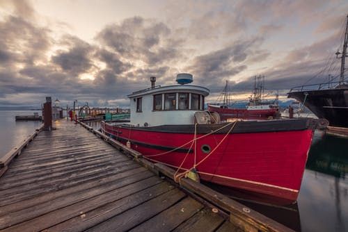 Red and White Boat on Dock Under Cloudy Sky