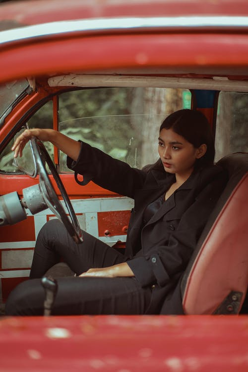 Woman in Black Outfit Sitting on Red Car Seat
