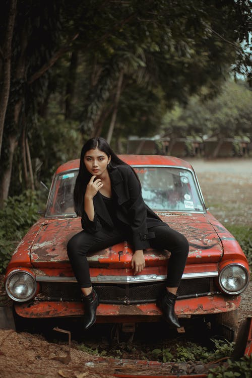 Woman in Black Outfit Sitting on Red Car
