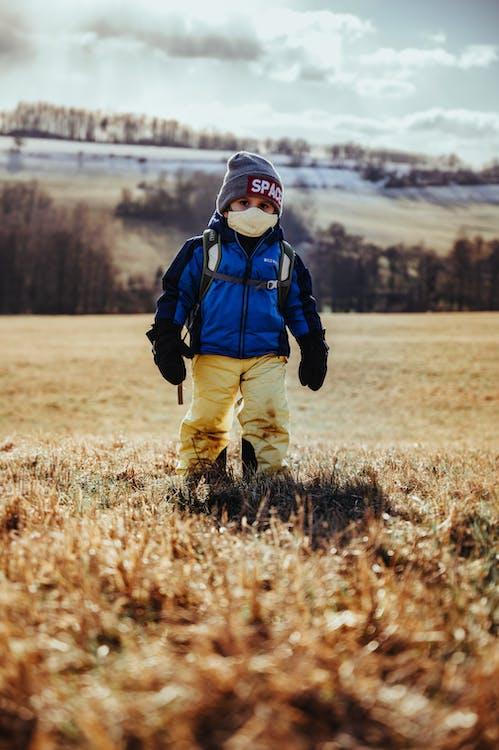 Kid in Blue Jacket and Brown Pants Walking on Brown Grass Field