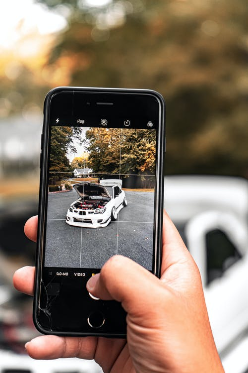 Person Holding Black Iphone 5 Showing White Car