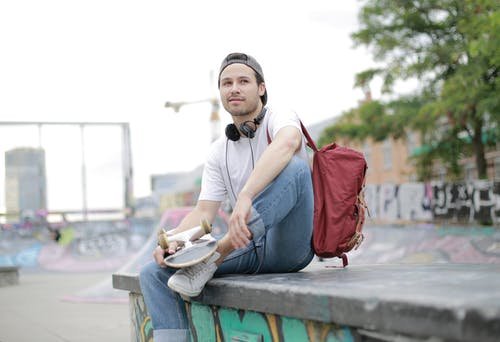 Man in White Shirt and Blue Denim Pants Sitting on Concrete Ramp