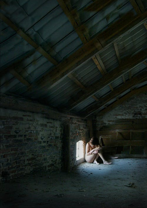Naked Woman Sitting on Floor Near the Window