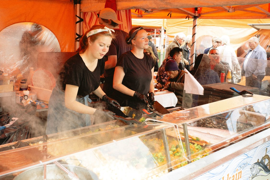 Women in Black Shirt Selling Food in Food Stall