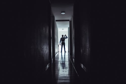 Silhouette of Person with Sword and Shield Walking on Hallway