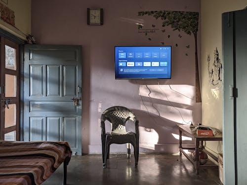 Black Flat Screen Tv Turned on Near Green Plastic Armchair