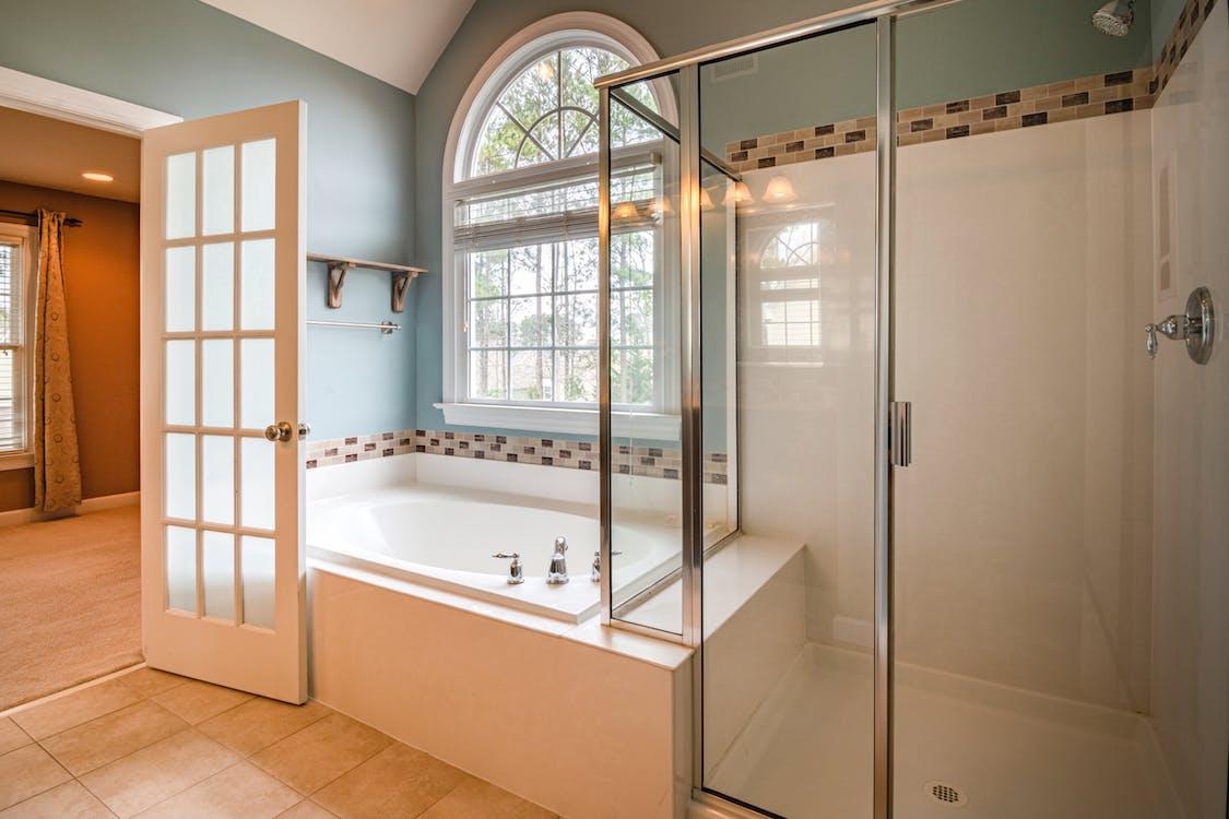 White Ceramic Bathtub Near White Framed Glass Window