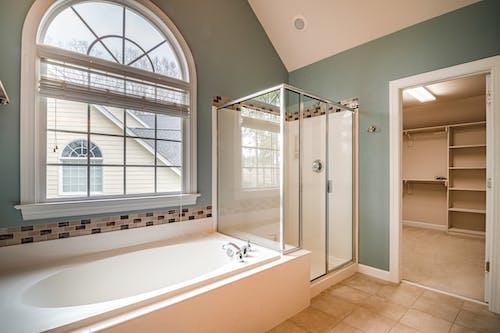 White Bathtub Near White Framed Glass Window