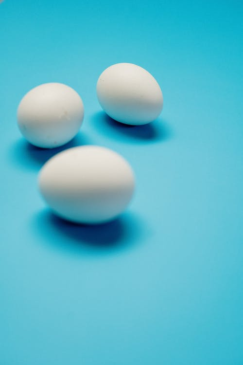 3 White Eggs on Blue Surface