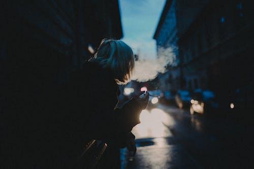Woman in Black Jacket Standing on Sidewalk Smoking