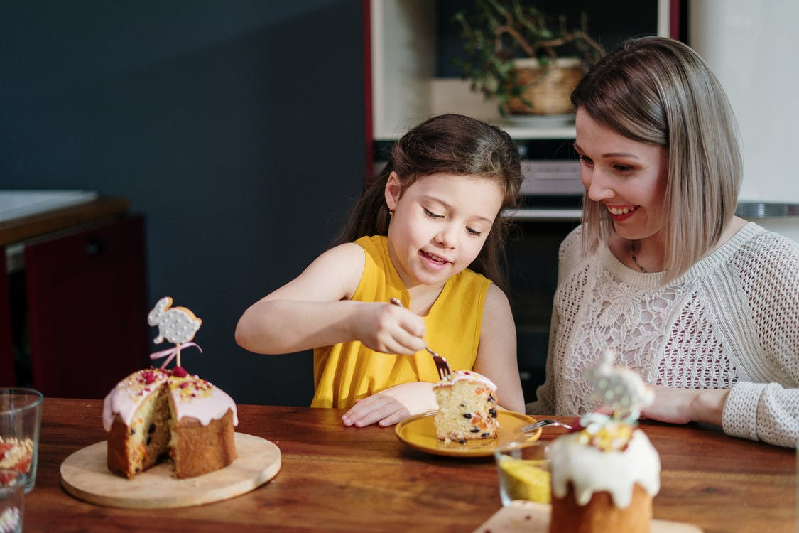 Mom and Daughter Eating Cake on Brown Wooden Table