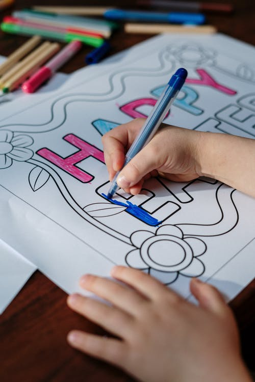 Kid Coloring Happy Easter on White Paper