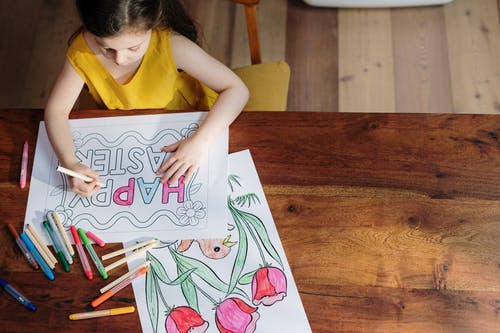 Girl in Yellow Tank Top Coloring on White Paper