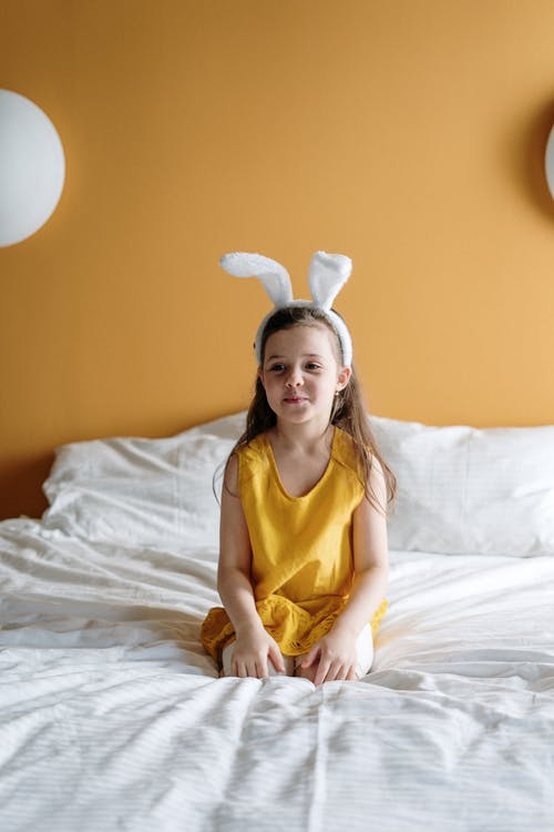 Girl in Yellow Top Sitting on Bed