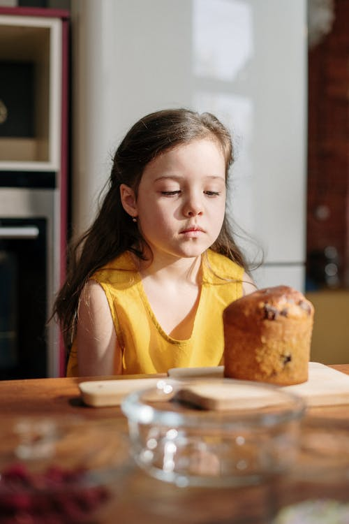 Girl in Yellow Shirt Sitting by the Table With Bread on Plate