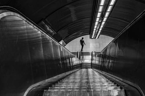 Person Walking on Tunnel in Grayscale Photography