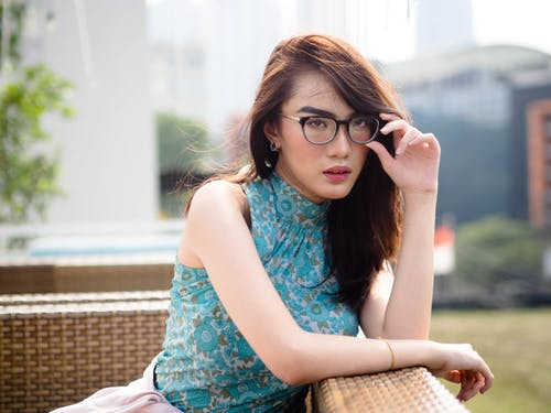 Woman in Blue Tank Top Wearing Black Framed Eyeglasses