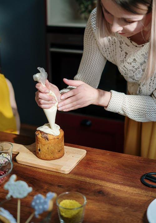 Woman in White Knit Sweater Holding White Piping Bag