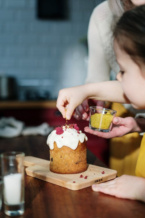 Girl in Yellow Shirt Decorating Brown Cake