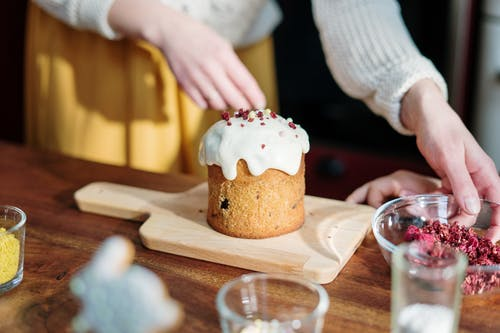 Person Holding Brown Cupcake With White Icing on Brown Wooden Table
