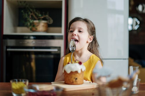 Girl in Yellow Shirt Licking Icing on Spoon