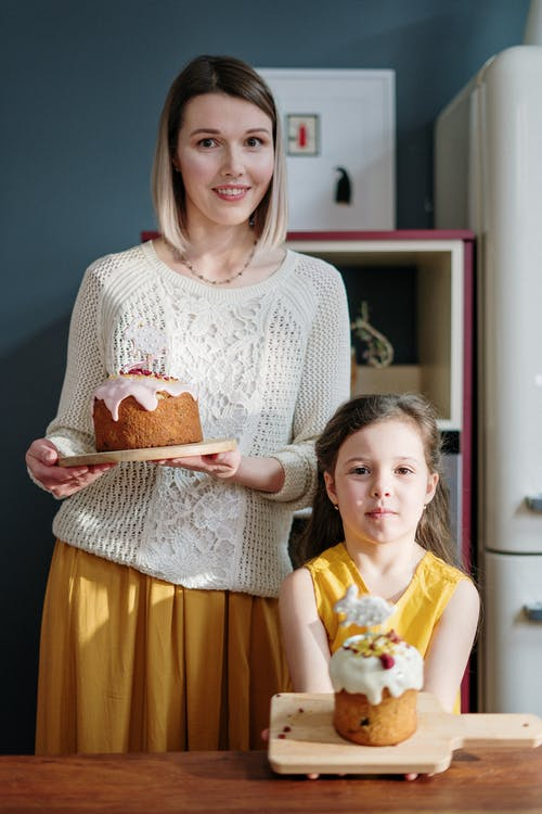 Woman in White Knit Sweater and Little Girl Holding Cake