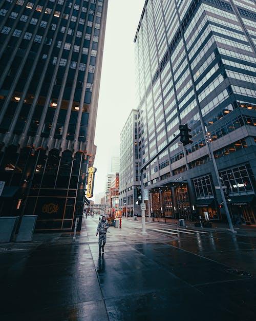 Man Walking on Sidewalk Near High Rise Buildings