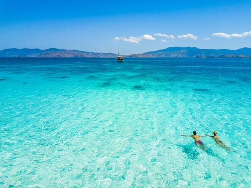 Couple Swimming in Blue Sea Under Blue Sky