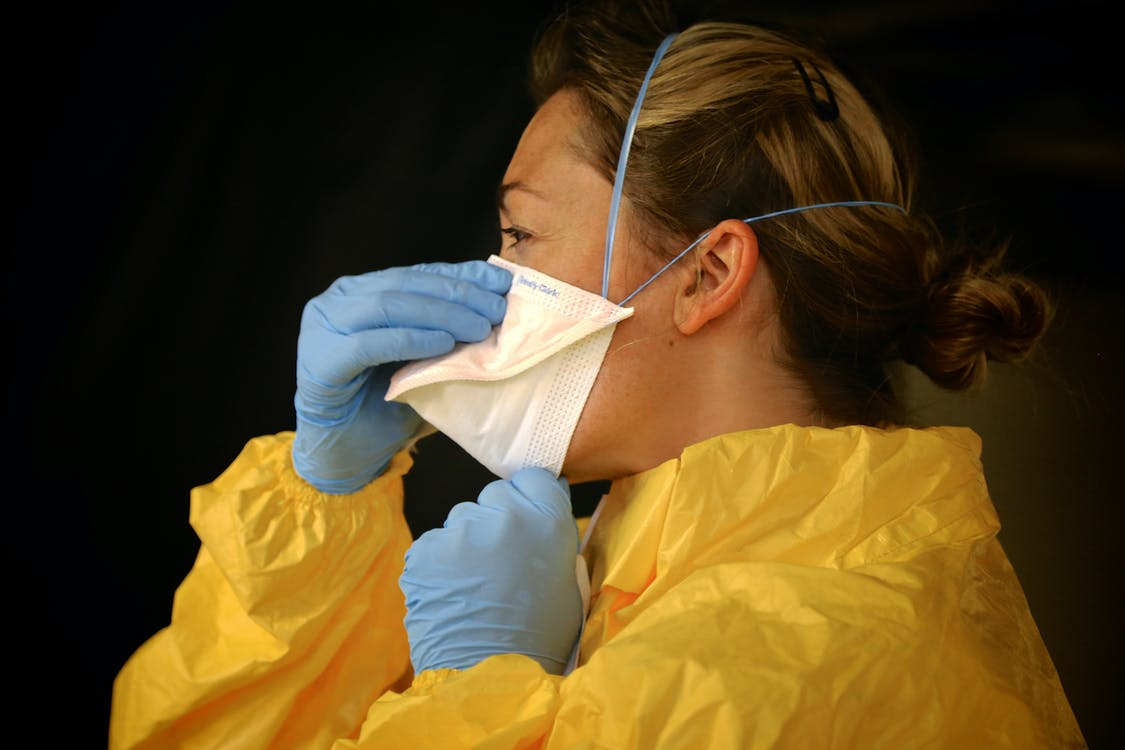 Woman in Yellow Protective Suit Wearing White Face Mask