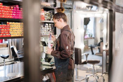 Woman in Brown Jacket Standing Near Glass Door