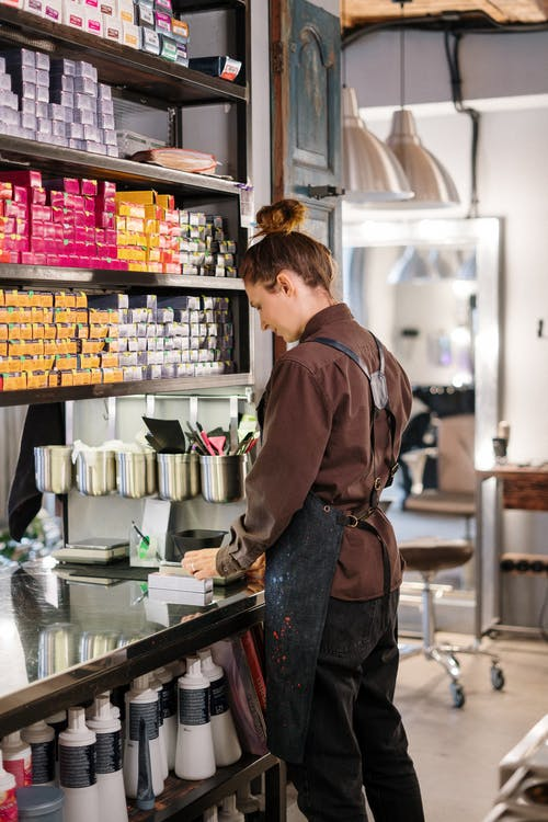 Woman in Brown Jacket Standing in Front of Counter