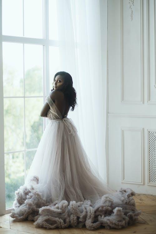 窓の近くに立っている白いウェディングドレスの女性