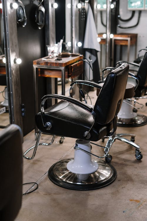 Black Leather Barber Chair in Front of Mirror