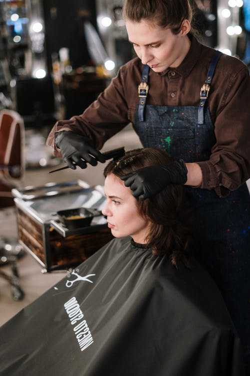 Woman in Black Leather Jacket Cutting Hair of Woman in Blue Denim Jacket