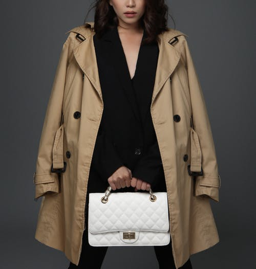 Woman In Brown Coat Holding A Bag