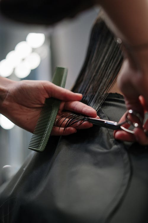 Person Holding Black Hair Comb