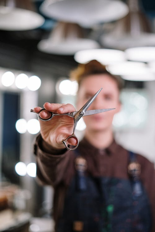 Person in Brown Long Sleeve Shirt Holding Silver Scissors