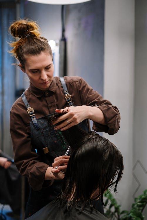 Woman in Brown Jacket Holding Black Hair