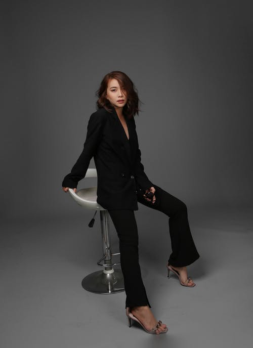 Woman in Black Blazer and Black Pants Sitting on Bar Stool