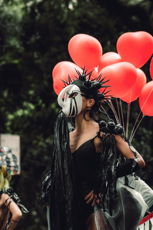 Woman in Black Dress Costume Holding Balloons