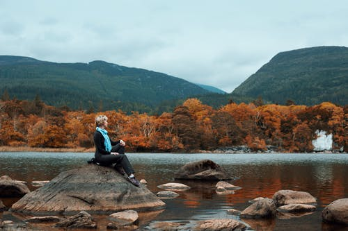 Woman Sitting on Rock Near River