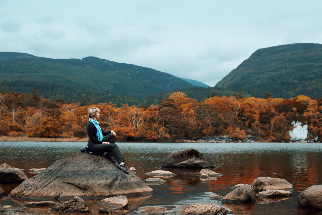 Woman Sitting on Rock Near River