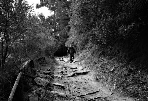 Grayscale Photo of Man in Black Jacket and Pants Walking on Dirt Road