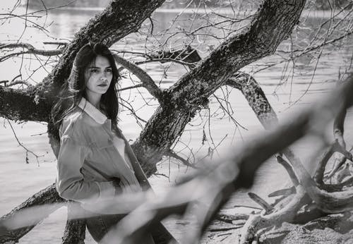 Grayscale Photo Of Woman Standing Beside Tree