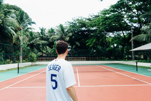 Man in White and Blue Jersey Shirt Standing on Tennis Court