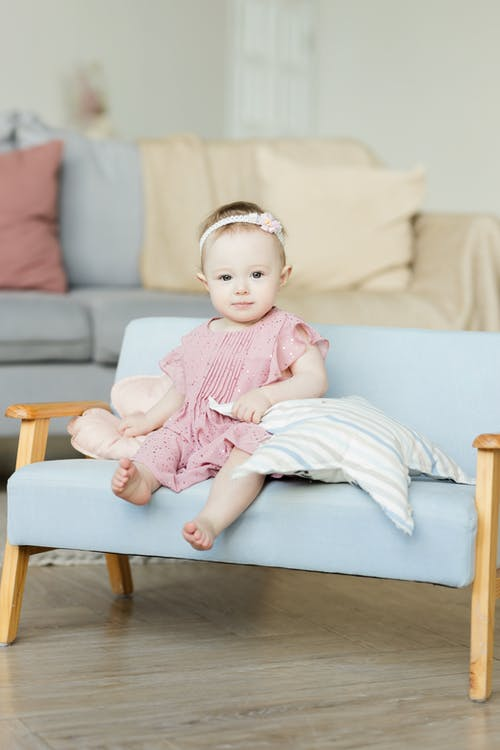 Baby Girl in Pink Dress Sitting on Sofa